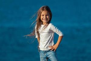 Adorable happy smiling little girl on beach vacation. jeans