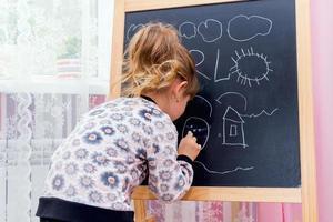 Little beautiful girl drawing on a blackboard. photo