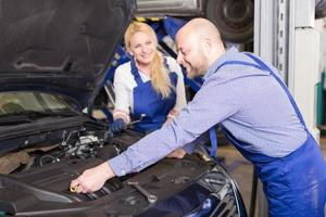 mechanic and assistant working at auto repair shop photo