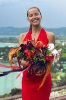 mujer de moda en vestido rojo con flores posando en tropical