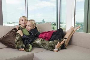 hermanos cariñosos en disfraces de dinosaurios y vampiros en casa foto