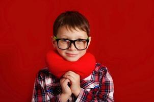 menino de óculos com um coração de brinquedo