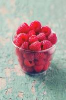 raspberry in a glass bowl on wooden surface