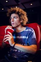 joven viendo una película y bebiendo refrescos