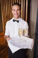 Guapo camarero sonriente sosteniendo una bandeja de champán foto