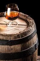 Glass of aged cognac and old wooden barrel