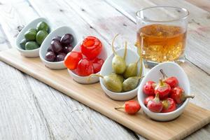 Selection of olives and peppers with whiskey photo