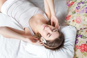 The young girl in bed listening to music headphones photo