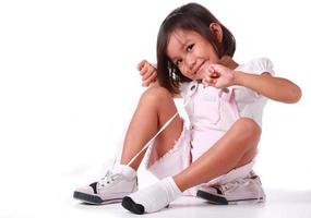 little girl making a tie on her shoe photo