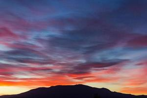 Colorful sunset clouds over mountain photo
