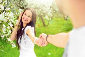 mujeres jóvenes felices en el jardín con flores de manzana foto