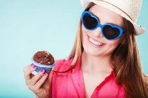 sonriente mujer de verano sostiene la torta en la mano foto