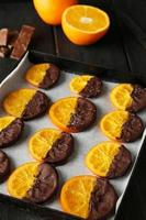 Delicious slices of orange coated chocolate on plate photo