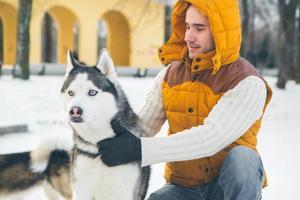 Hombre caminando con perro en invierno con nieve foto