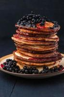 Pancakes with fresh berries and blueberry jam on wooden table