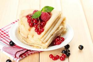 Delicious pancakes with berries and jam on plate isolated white