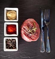 Fresh raw beef steak on black stone