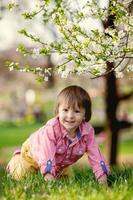 Adorable happy kid outdoors on spring day in beautiful blooming