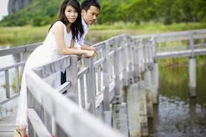 Beautiful married couple on the wooden bridge.