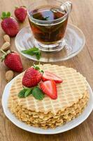 Homemade waffle with strawberry on a wooden surface