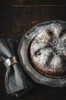 Cake with icing sugar with napkin in metal ring vertical