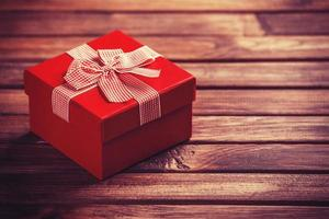 Red gift box on wooden table.