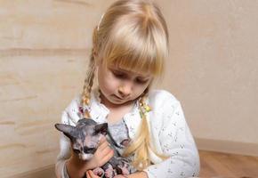 niña rubia sosteniendo un gatito sphynx
