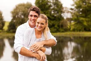 young couple hugging by the lake