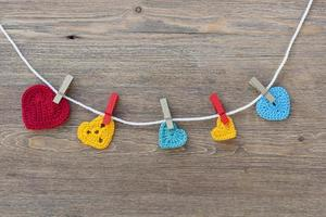 Many multicolor crochet hearts on wooden background for Valentines day