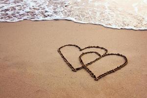 twee harten getekend in zand op een strand
