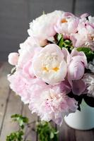 Bunch of peony flowers  in an enamel jar photo