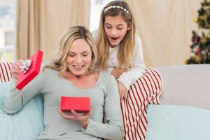madre abriendo regalo de navidad con hija foto