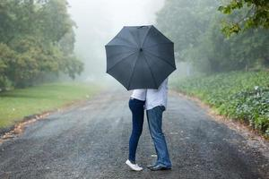 couple kissing behind the umbrella photo