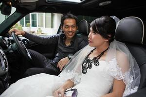 gorgeous wedding couple in car photo