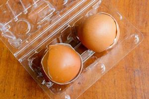 Broken brown eggs in the plastic box on wooden background