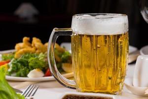 Jarra de refrescante cerveza fría en la mesa foto