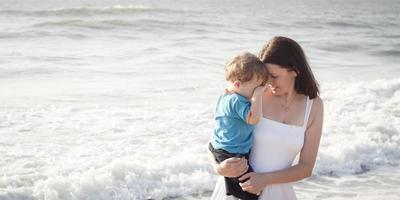 madre joven con hijo jugando en la playa