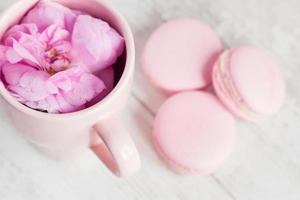 Tea cup with rose and macaroons, selective focus photo