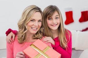mãe festiva e filha sorrindo para a câmera
