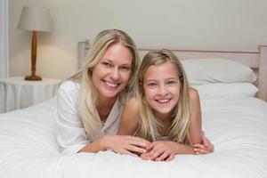 mulher com filha deitada na cama em casa
