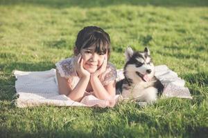 Hermosa chica asiática recostada sobre la hierba verde con un siberiano foto