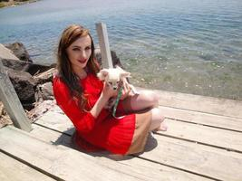 Girl in red dress and chihuahua by the water photo