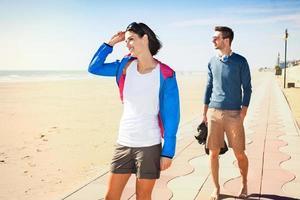 Pareja de jóvenes turistas de pie en un paseo marítimo de la playa foto