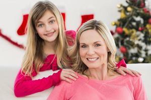 madre e hija festivas en el sofá foto
