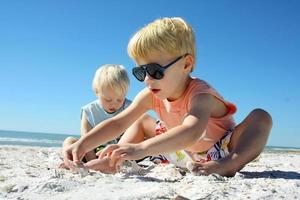 dos niños jugando en la arena en la playa foto