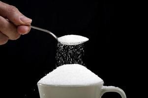 Mano de hombre con cuchara vertiendo azúcar loco en la taza de café foto