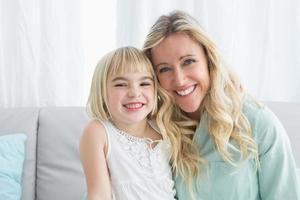 madre sentada en el sofá con su hija foto