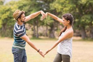 linda pareja en el parque haciendo forma de corazón
