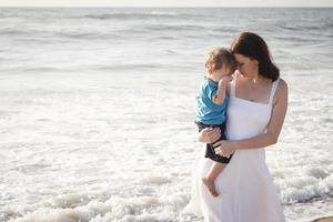 madre joven con hijo jugando en la playa foto