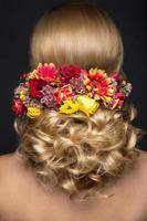 Beautiful blond woman in image of the bride with flowers